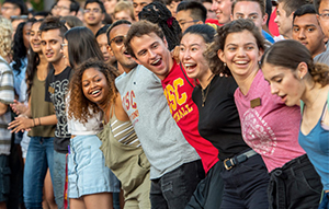A line of USC students with arms interlocked participating in a welcome week event on campus.